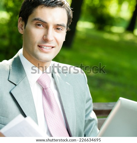 Young happy smiling business man working with laptop, outdoors