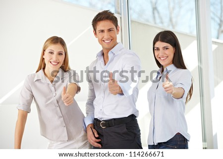 Young happy smiling business team holding their thumbs up - stock photo