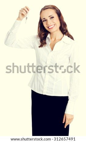 Young happy smiling business woman or real estate agent showing keys from new house - stock photo
