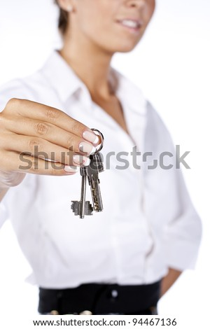 Young happy smiling business woman or real estate agent showing keys from new house, isolated on white background - stock photo