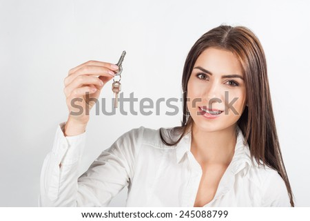 Young happy smiling business woman or real estate agent showing keys from new house, isolated over white background - stock photo