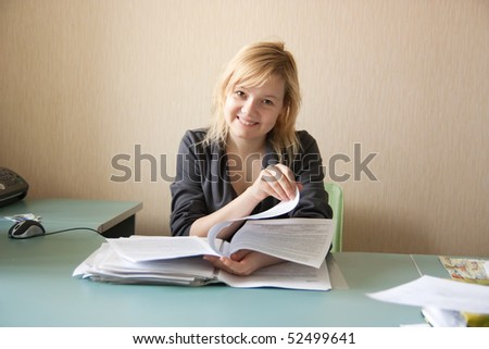 Young happy smiling businesswoman sitting in office