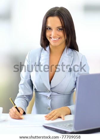 Young happy smiling businesswoman working at office - stock photo
