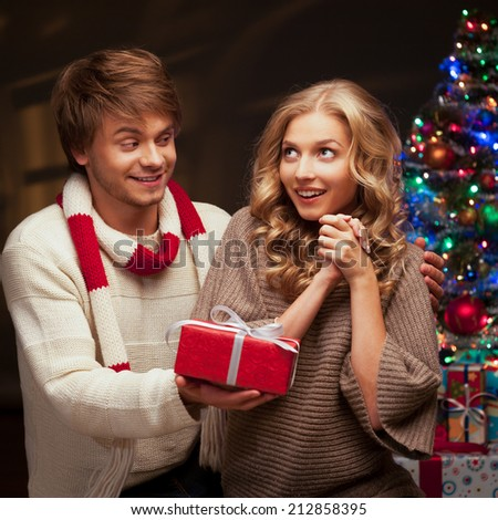 young happy smiling casual couple presenting red gift over christmas tree and lights on background. warm light - stock photo
