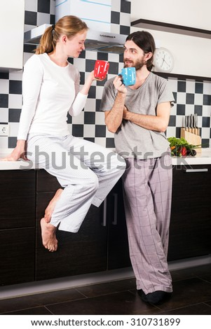 young happy smiling caucasian couple on kitchen drinking morning coffee and talking to each other