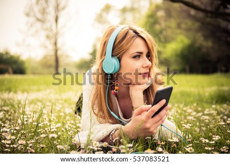 Young happy smiling caucasian woman listening music with headphones from her smart phone at the park during a sunny day wearing casual clothes