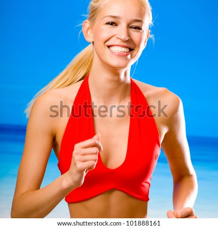 Young happy smiling cheerful blond woman in sports wear running on beach - stock photo