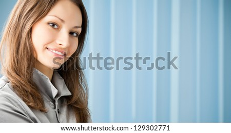 Young happy smiling cheerful business woman at office, with copyspace. To provide maximum quality, I have made this image, by combination of two photos. - stock photo