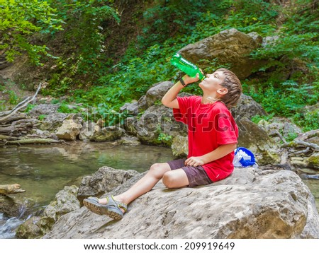 young happy smiling child boy drinking water on forest river background - stock photo