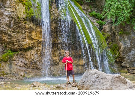 young happy smiling child boy on waterfall background - stock photo