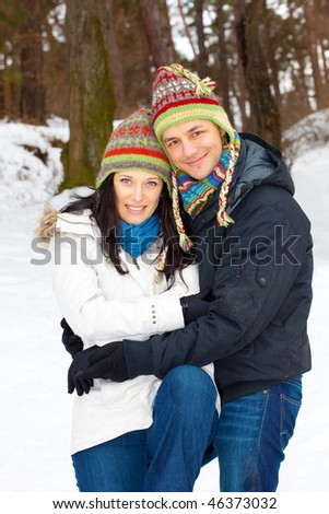 Young happy smiling couple outside during wintertime. - stock photo
