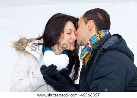 Young happy smiling couple outside with a heart shape snowball - stock photo