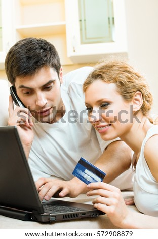 Young happy smiling couple with laptop, paying by credit card in internet store, at home