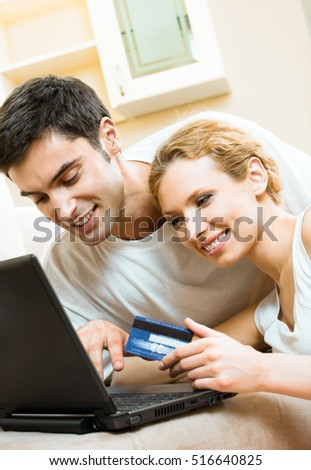 Young happy smiling couple with laptop, paying by credit card in internet store, at home. Love, relations, romantic concept shoot.
