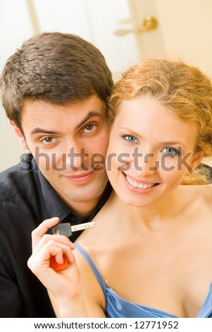 Young happy smiling family with a key at new home - stock photo