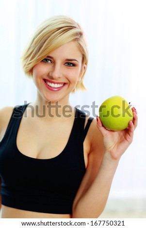 Young happy smiling fit woman holding green apple - stock photo