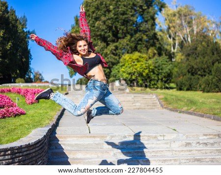 Young happy smiling girl dancing on the street in a plaid shirt  - stock photo