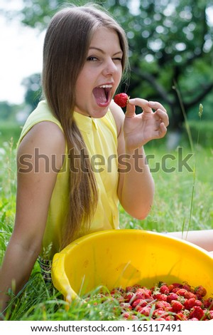 Young happy smiling girl eating strawberry on green summer outdoors background - stock photo