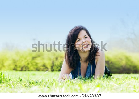 Young happy smiling girl lying on grass