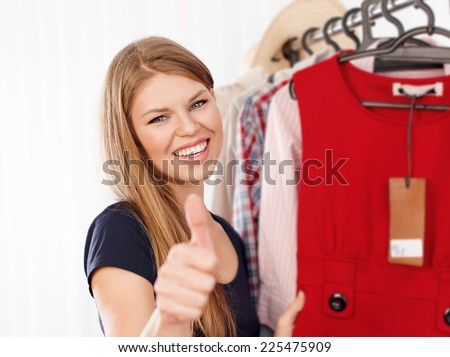 Young happy smiling lady fashion shop owner showing thumb up indoors in the store. Portrait of attractive female small business proprietor standing at clothes rack.  - stock photo
