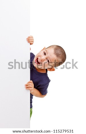 Young happy smiling little boy look outs from the blank billboard - stock photo
