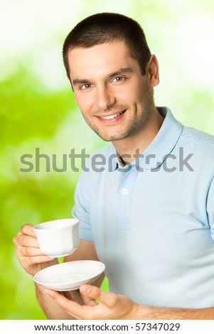 Young happy smiling man drinking coffee, outdoors - stock photo