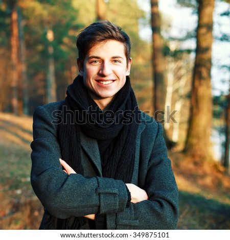 Young happy smiling man posing in cold winter park  - stock photo