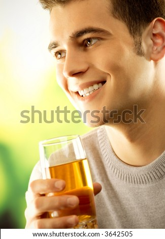 Young happy smiling man with glass of fruit juice, outdoors