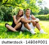 Young happy smiling sporty couple sitting on a meadow in a park - stock photo