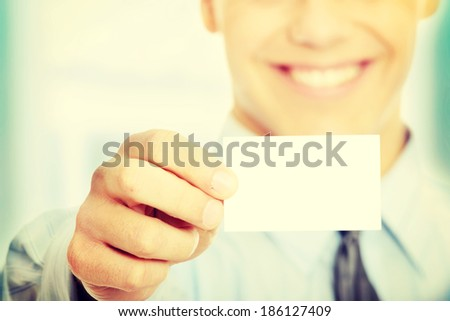 Young happy smiling successful business man with blank business card or sign  - stock photo