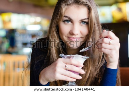 Young happy smiling woman beautiful girl having fun eating ice cream in cafe closeup portrait - stock photo