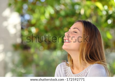 Young happy smiling woman doing deep breath exercises outdoor with a green background            - stock photo