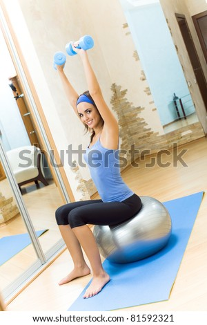 Young happy smiling woman doing fitness exercises with fit ball and dumbbells at home - stock photo