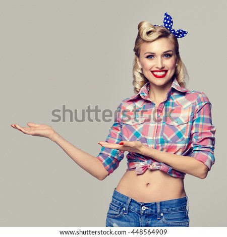 Young happy smiling woman, dressed in pin-up style, showing something or copyspace area for text or slogan. Caucasian blond model posing in retro fashion and vintage concept studio shoot. - stock photo