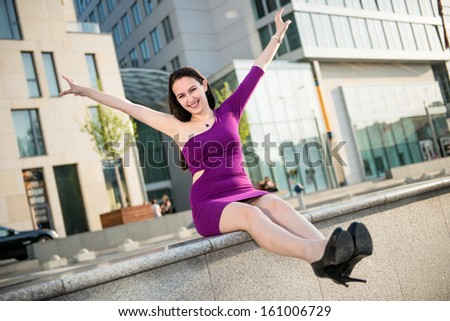 Young happy smiling woman enjoying life - stretching hands and legs - stock photo