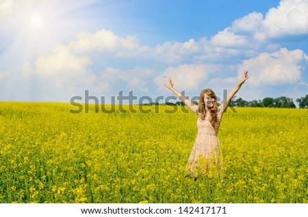 Young happy smiling woman having fun at canola field
