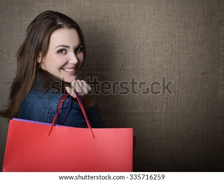 Young happy smiling woman holding red and purple shopping bags over canvas, image toned. - stock photo