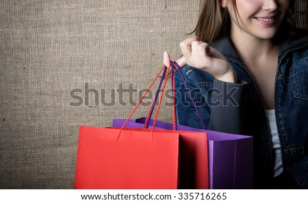 Young happy smiling woman holding red and purple shopping bags over canvas, image toned.