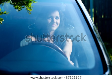 Young happy smiling woman in black car - stock photo