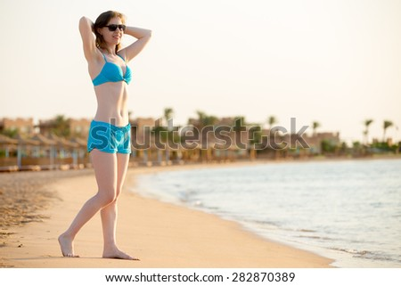 Young happy smiling woman in sunglasses and swimwear standing barefoot in relaxed pose on the beach, basking in sunlight on tropical sea resort - stock photo