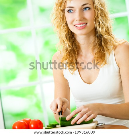 Young happy smiling woman making fegetarian salad at home - stock photo