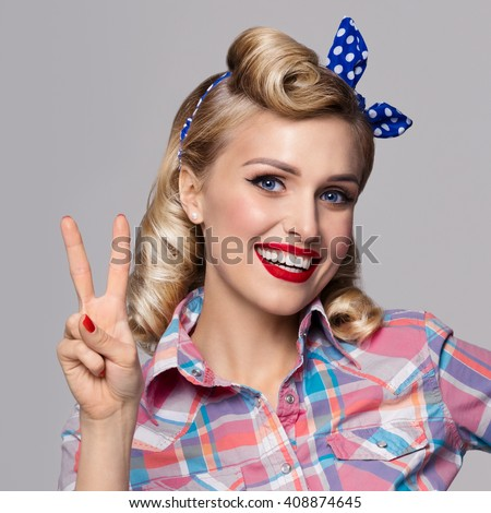 Young happy smiling woman, showing two fingers or victory gesture, dressed in pin-up style. Caucasian blond model posing in retro fashion and vintage concept studio shoot, on grey background.