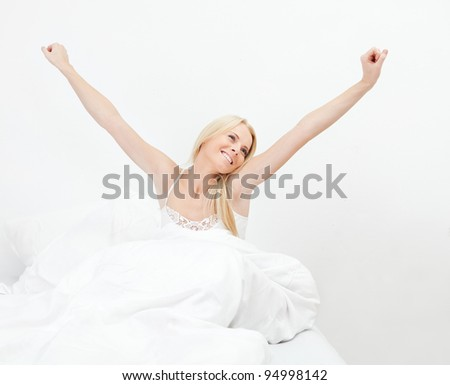 Young happy smiling woman waking up - stock photo
