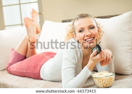 Young happy smiling woman watching TV and eating popcorn at home - stock photo