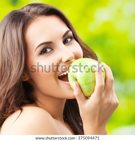Young happy smiling woman with green apple - stock photo