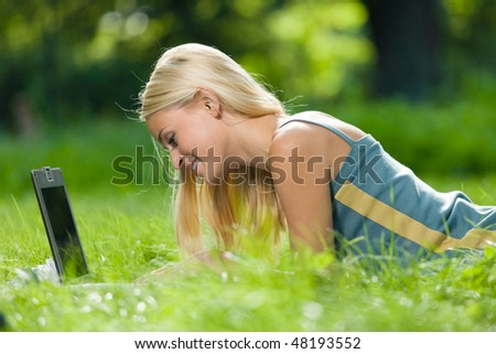 Young happy smiling woman with laptop, outdoors - stock photo
