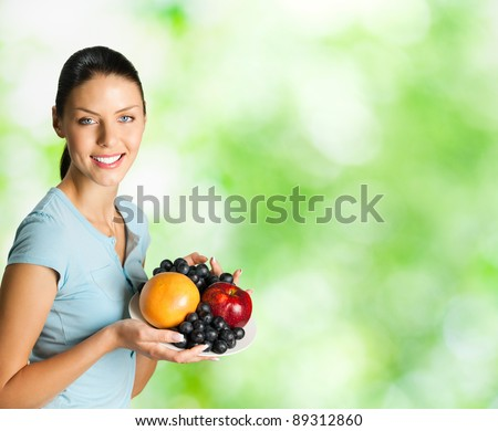Young happy smiling woman with plate of fruits, outdoor. To provide maximum quality, I have made this image, by combination of two photos. You can use right part for slogan, big text or banner. - stock photo