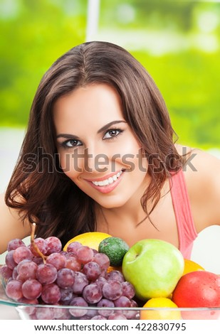 Young happy smiling woman with plate of fruits, outdoors - stock photo
