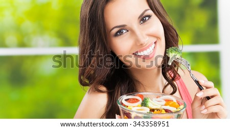 Young happy smiling woman with salad, outdoor, with copyspace - stock photo