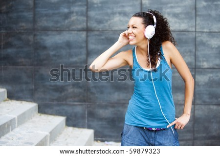 Young happy sportive woman in urban background listening music - stock photo